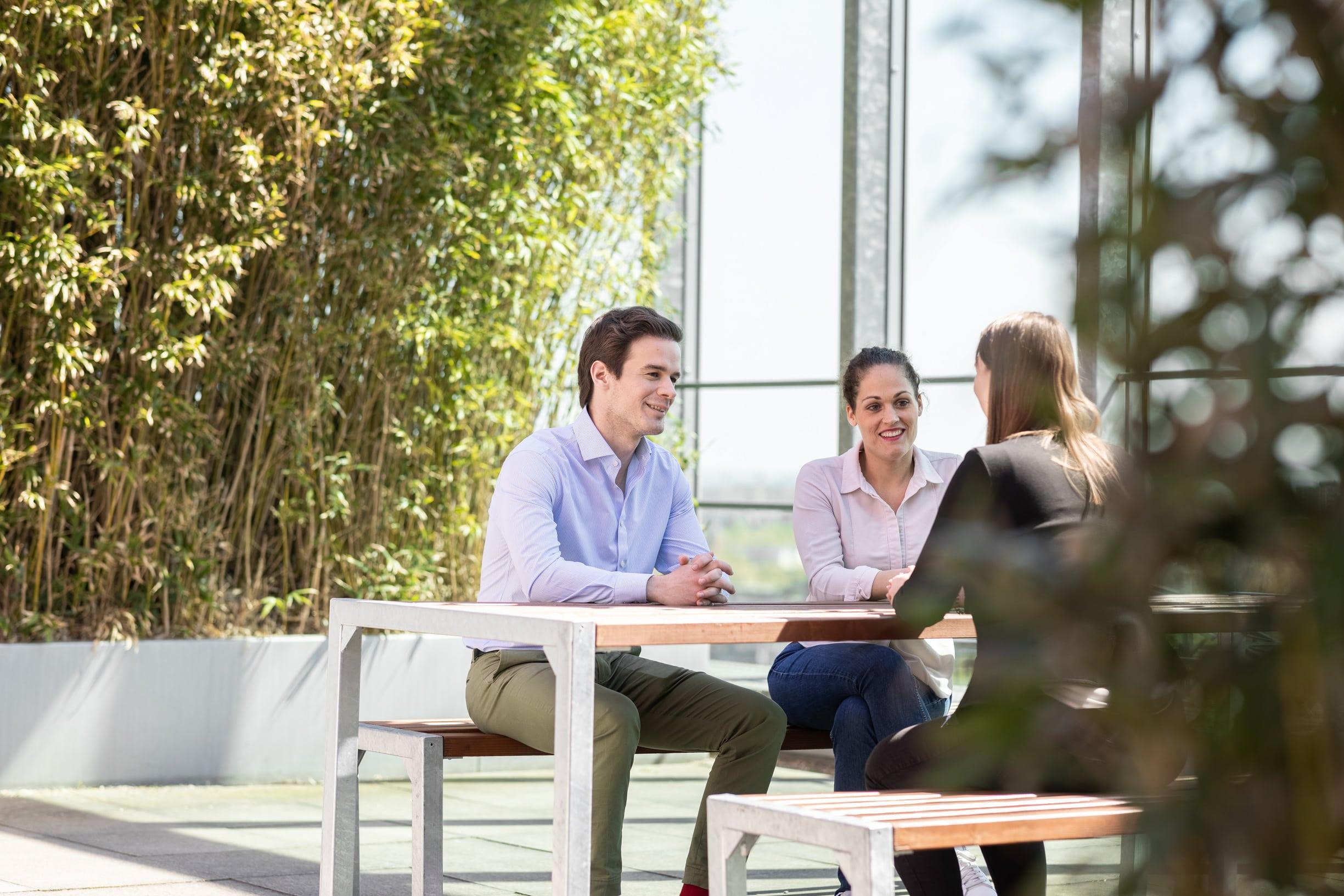 Eine Gruppe von Menschen sitzt an einem Tisch und unterhält sich